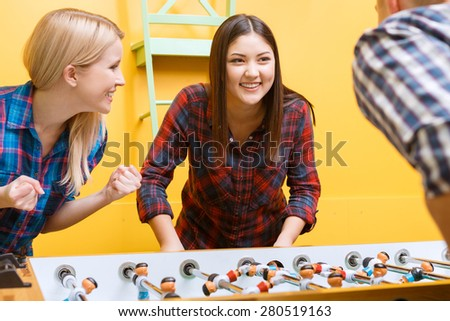 Lets play. Beautiful young Asian girl looking smiling at her partner while playing air hockey wearing checkered shirt in a yellow room, her friend cheering her up - stock photo