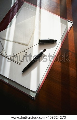 Letter and fountain pen on wood table - stock photo