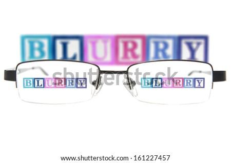 Letter blocks spelling blurry through glasses. Isolated on white - stock photo