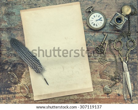 Letter paper and vintage writing tools. Feather pen, inkwell, keys on textured wooden background. Retro style toned picture - stock photo
