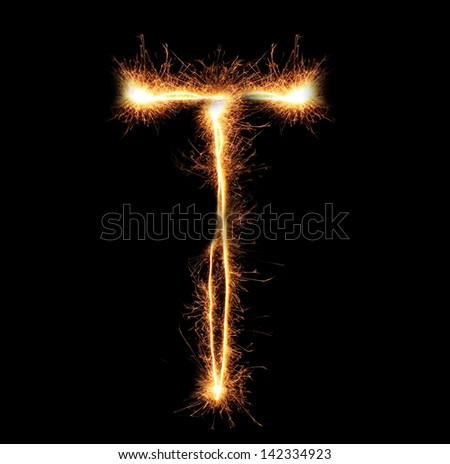 "Letter ""T"" sparklers on black background - stock photo"