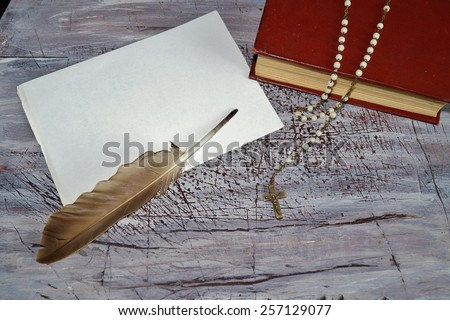 Letter to God and rosary over an old holy bible  - stock photo