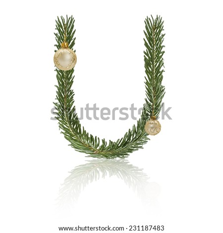Letter U made from fir branches, decorated with christmas balls and reflection. - stock photo