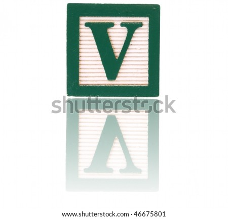 letter v in an alphabet wood block on a reflective surface - stock photo