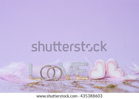 letters spelling the word Love with wedding rings on pink background with pantone color style , Wedding, Valentine, Engagement, Anniversary theme - stock photo