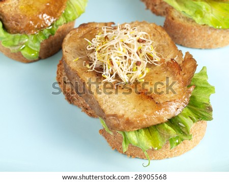 Lettuce, fried seitan slice and grown soy shoots with bread,  tapa appetizer - stock photo
