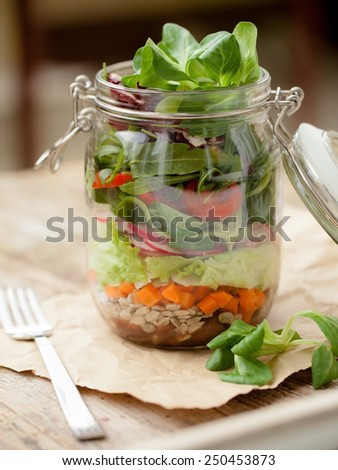 Lettuce, tomato and other vegetables in glass jar - stock photo
