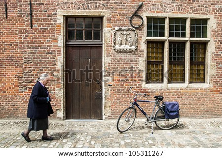 LEUVEN, BELGIUM - JUNE 10th, 2012: Old lady walks on a street of Grand Beguinage of Leuven, Belgium on 10 June 2012. Grand Beguinage is a tourist attraction included in the UNESCO world heritage list - stock photo