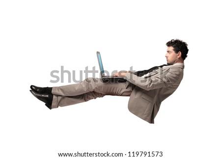 Levitating businessman using a laptop computer - stock photo