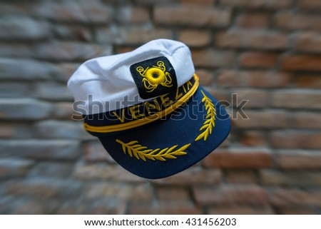 Levitating Venezia navy hat in front of blurred brick wall with zoom effect. Standard souvenir cap from Venice flying in front of brick wall with zoom effect. - stock photo