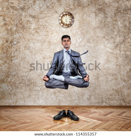 Levitation by Indian businessman in lotus pose in the office near the wall with clock and his shoes on the floor - stock photo