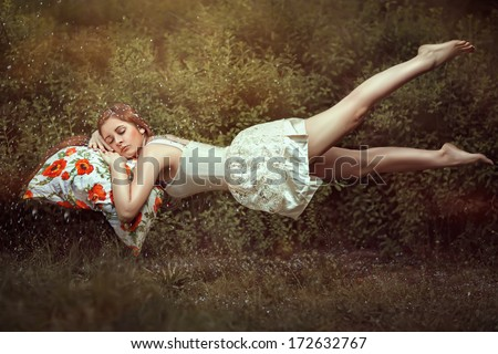 Levitation girl on the pillow. Sweet dream girls dream of flight. - stock photo