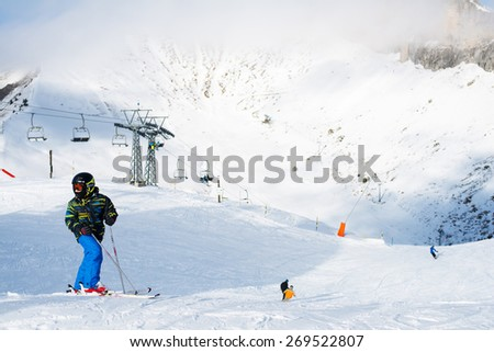 LEYSIN, SWITZERLAND - 29 DECEMBER 2013 : boy in ski goggles looking into the distance on the background of a ski resort in Leysin in the Swiss Alps - stock photo