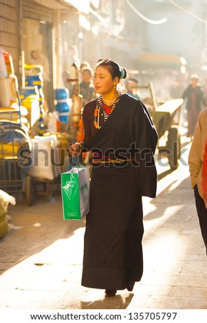 LHASA, CHINA - OCTOBER 17: A unidentified modern attractive young Tibetan woman walks the traditional Barkhor circuit, a famous tourist destination in Tibet on October 17, 2007 in Lhasa, China - stock photo