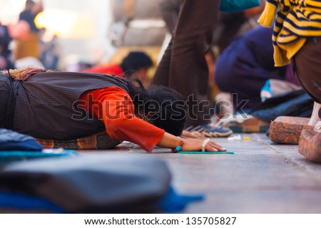 LHASA, CHINA - OCTOBER 17: An unidentified Tibetan prostrator lies flat on her stomach at Jokhang temple, a famous tourist, pilgrimage site in Tibet on October 17, 2007 in Lhasa, China - stock photo