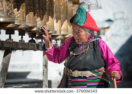LHASA - JUNE 5: Unidentified Tibetan pilgrim circles the Potala palace on June 5, 2013 in Lhasa, Tibet. Devotees walk 3 times around the Potala to accumulate karma (religious merit) and good luck. - stock photo