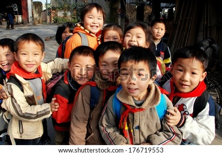 LI'AN VILLAGE, CHINA - NOVr 26, 2007:  Little Chinese school children gathered in a group are all smiles  - stock photo