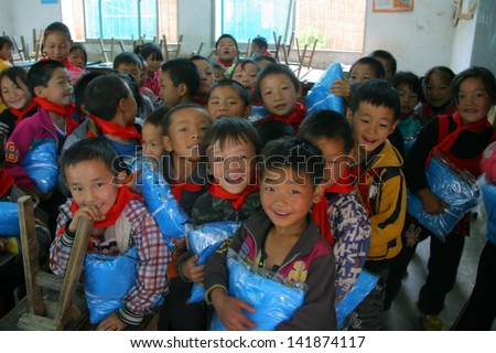 LIANGSHAN, CHINA - MAY 29: Unidentified children smile and laugh when they get their presents of Childrens Day, which donated by welfare organization on May 29, 2013, Liangshan, Sichuan, China - stock photo