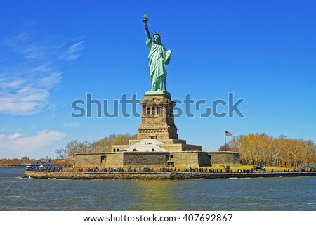 Liberty Island and Statue in Upper New York Bay, New York City, USA. In Upper New York Bay. Tourists are walking on the island. - stock photo