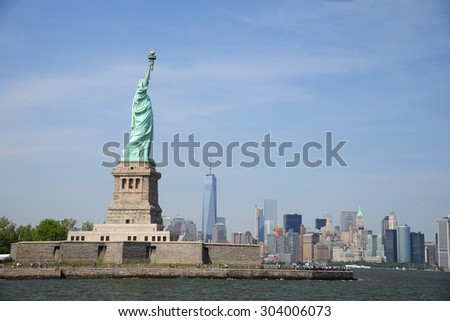 Liberty Statue with buildings in manhattan downtown new york as a background - stock photo