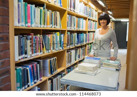 Librarian putting books back on shelf - stock photo