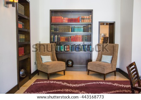 Library in luxury home with book shelf and comfortable chairs - stock photo