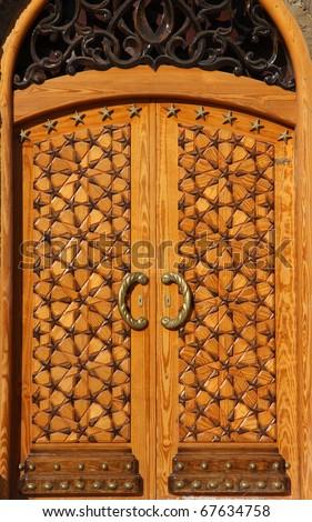 Libya Bengazhi beautiful crafted wooden arabesque door decorated with brass handles and islamic stars - stock photo