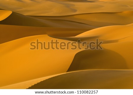 Libyan Desert. Dense gold dust, dunes and beautiful sandy structures in the light of the low sun. - stock photo