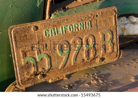 License plate on an old truck in an artichoke field near Santa Cruz, California. - stock photo