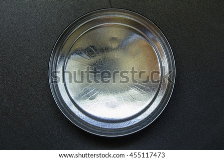 Lid or base of food tin can on black background - stock photo