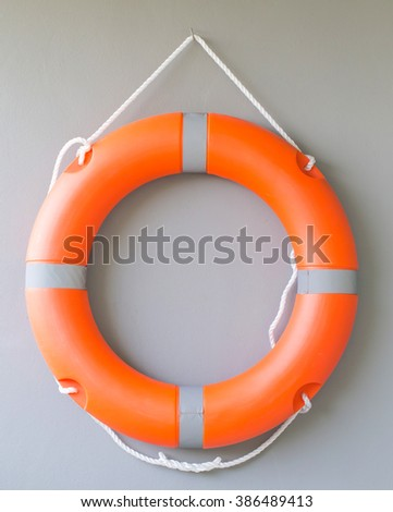 Life buoy on cement wall  background - stock photo