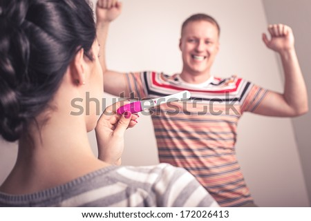 Life concept. Girl holding pregnancy test with negative result. Man with happy emotions. - stock photo