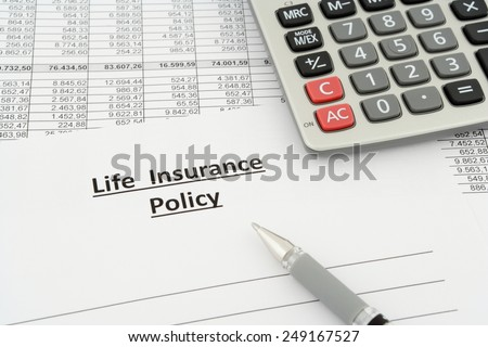 life insurance policy with calculator and pen - stock photo