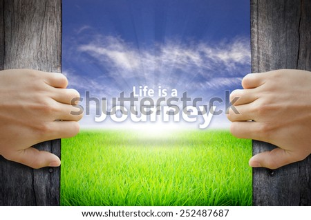Life is a Journey Inspirational quote. Hand opening an old wooden door and found a texts floating over green field and bright blue Sky Sunrise. - stock photo