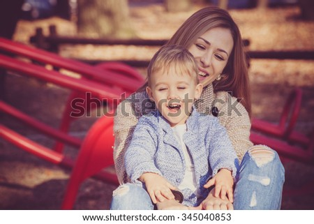 life is beautiful when you're a kid, child with his mother enjoy on roundabout in park, autumn day, selective focus - stock photo