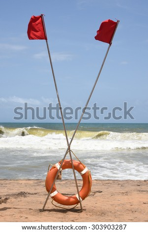 Life preserver on sandy beach, Kerala India.Swimming safety, two beach flags criss crossed in the sand.Red lifeguard flags shows safe place to swim.Blue ocean,surf,white foaming background,copy space - stock photo