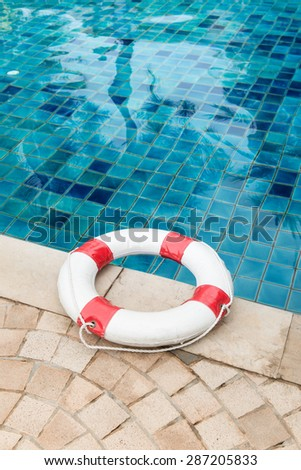 Life preserver white red lifebuoy with white ropes on tiled floor near swimming pool - stock photo