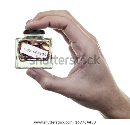 life savings, hand holding small jar of coins on white background - stock photo