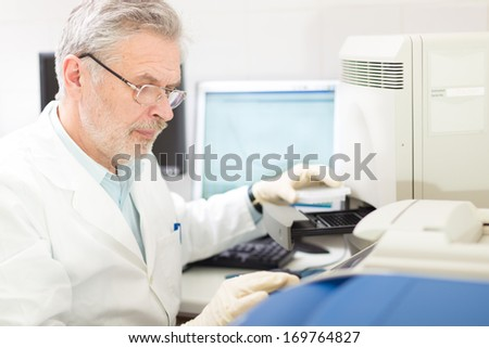 Life science researcher  performing a genotyping testing which enables personalized medicine. PM is a medical model that proposes the customization of health care. - stock photo