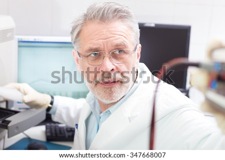 Life science researcher  performing a genotyping testing which enables personalized medicine. PM is a medical model that proposes the customization of healthcare. - stock photo