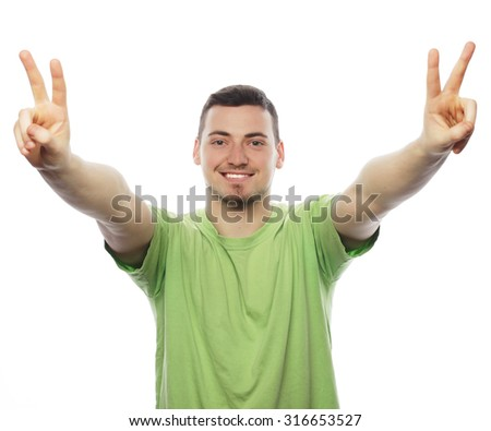 life style  and people concept: young casual man showing the victory gesture while smiling for the camera with a hand in his pocket.Isolated on white background - stock photo