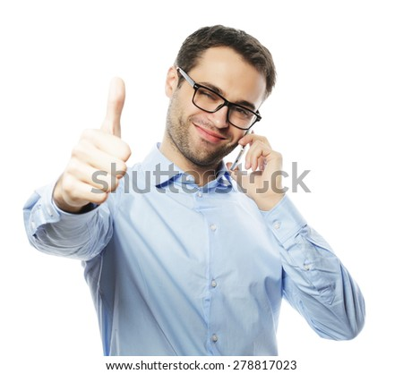 life style, business  and people concept: casual young man showing thumbs up sign, while speaking on the phone and smiling to the camera. Isolated on white background - stock photo