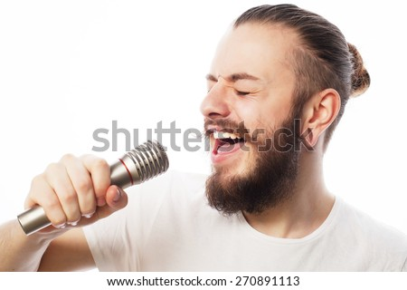 Life style concept: a young man with a beard wearing a white shirt holding a microphone and singing.Isolated on white. - stock photo