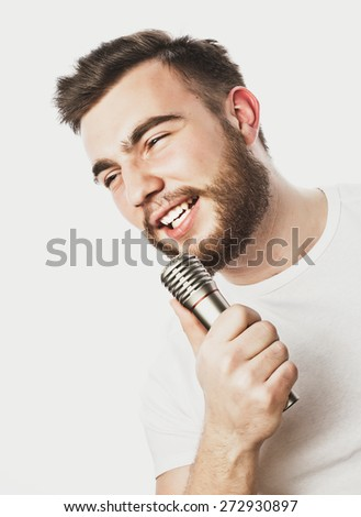 Life style concept: a young man with a beard wearing a white shirt holding a microphone and singing.Isolated on white. Fashionable toning picture. - stock photo