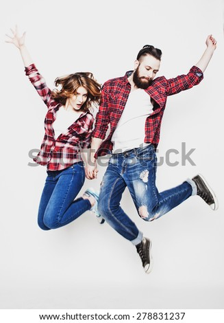 life style, happiness and people concept: Happy loving couple. Jumping over light grey background. Special Fashionable toning. - stock photo