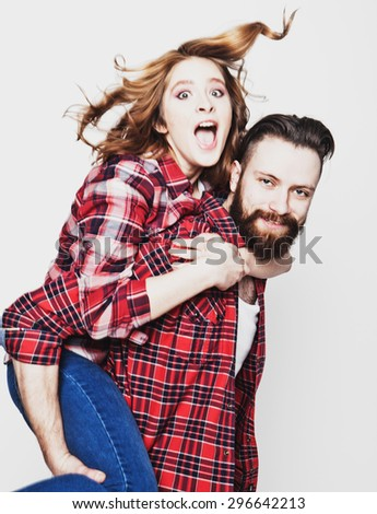 life style, happiness and people concept: Happy loving couple. Young man piggybacking his girlfriend. Studio shot over white background.Special Fashionable toning photos. - stock photo