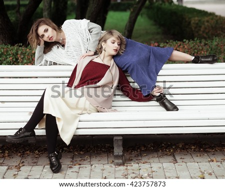 life style, happiness, emotional and people concept: beautiful young women sitting on a bench in the autumn park - stock photo