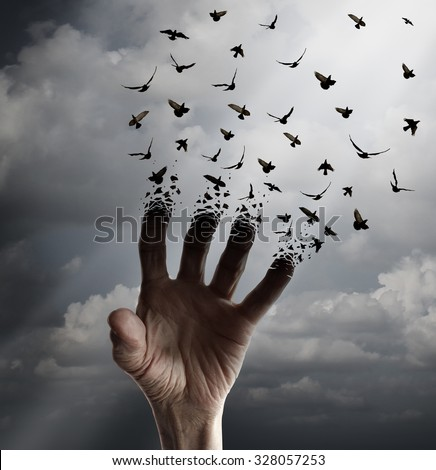 Life transformation concept as a hand reaching out transforming into flying birds following sunlight as a freedom symbol of hope renewal and spirituality or human faith. - stock photo