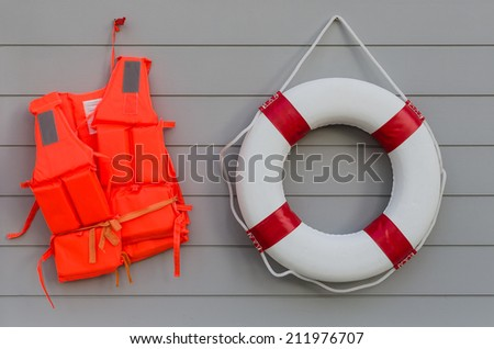 life vest and life belt on wooden wall - stock photo