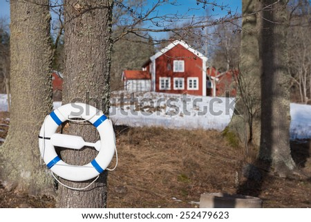 Lifebelt attached to a tree on the shore of a lake. In the background old red wooden farm house under a clear blue sky in winter. - stock photo